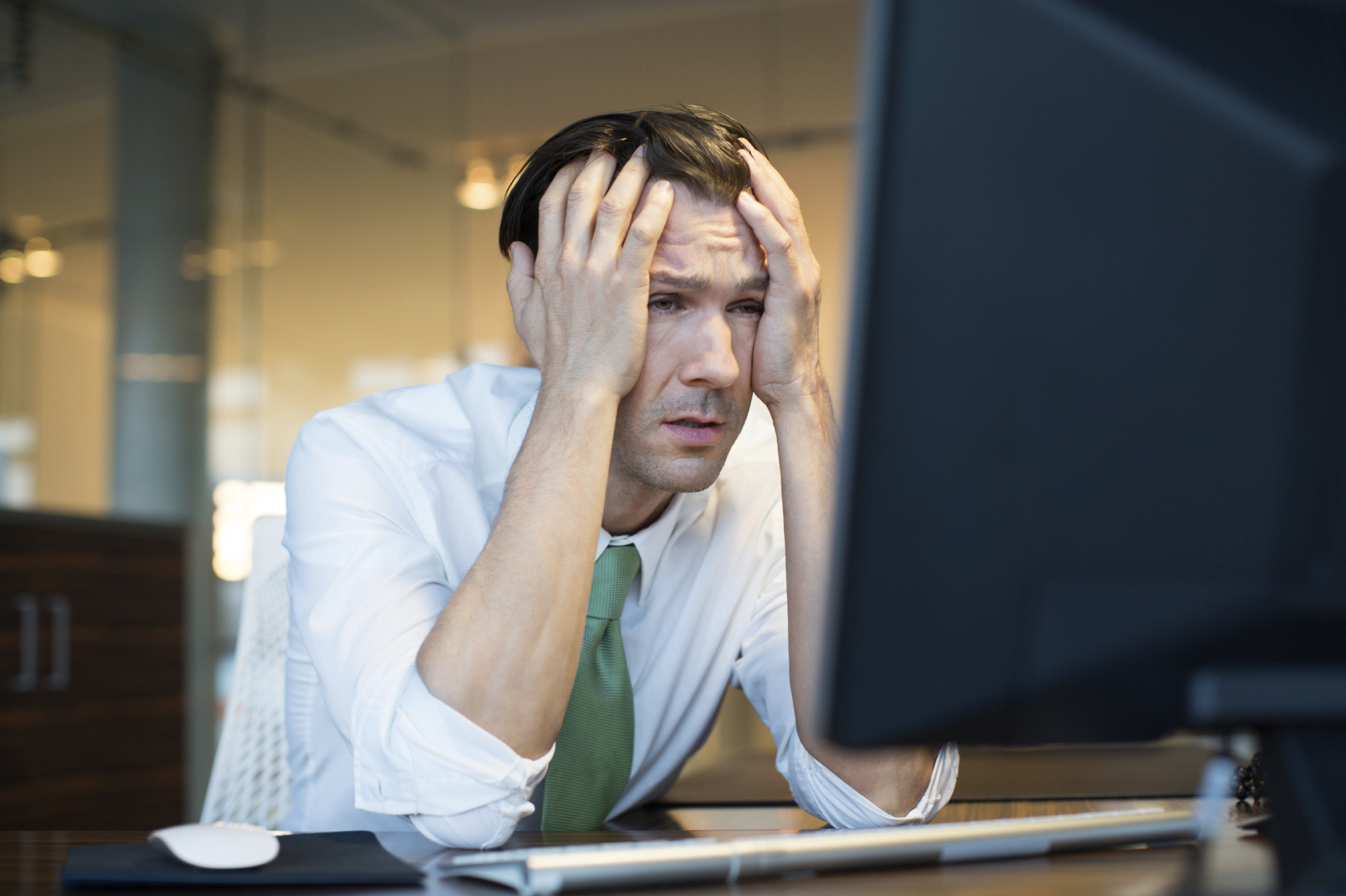 Man with headache for blog - fluorescent lighting decreases work office productivity
